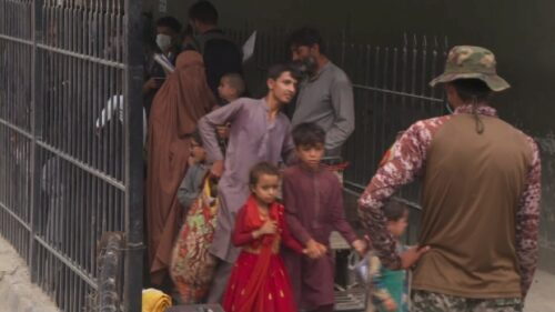 Afghan families move through mountain pass into Pakistan on their journey to Canada
